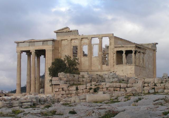 Erechtejon od zachodu; widoczne kolumny portyku północnego, ściana zachodnia, ganek Kor, a także oliwka rosnąca w tym samym miejscu co święte drzewko Ateny. W pasie fryzu widać niebieskawe zabarwienie zastosowanego jako tło kamienia.