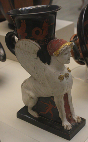 Rhyton w kształcie sfinksa z czerwonofigurową dekoracją na szyi oraz podstawie. Na szyi przedstawiony został Kekrops, mityczny król-wąż Aten z dziećmi i boginią tęczy Iris, na podstawie Aglauros, żona Kekropsa, oraz satyrowie. Ateny, ok. 470-460 BC, garncarz Sotades i Malarz Sotadesa. British Museum, Londyn.
