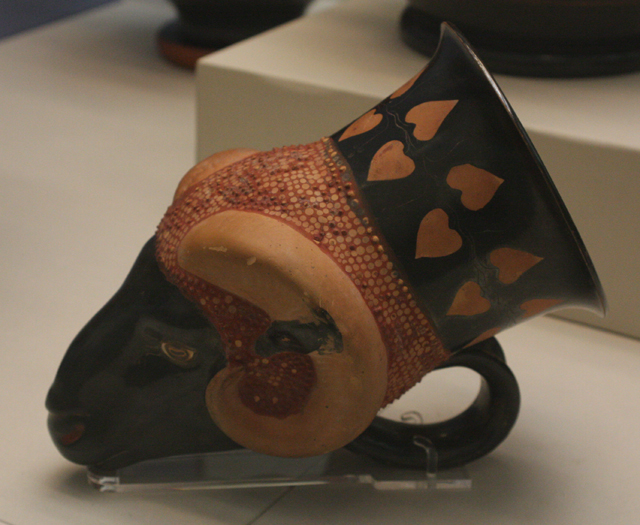 Rhyton (specjalne naczynie rytualne lub służące do picia wina) w kształcie głowy barana, wzorowany na srebrnych rhytonach perskich w tym kształcie;na szyi ornament z liści bluszczu. Ateny, ok. 470-460 BC, przypisywany garncarzowi Sotadesowi. British Museum, Londyn.