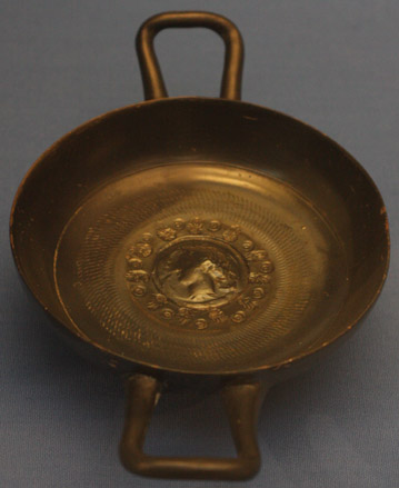 Kyliks bez nóżki, ceramika z czarnym slipem, z reliefowym, wzorowanym na wizerunku monetarnym, przedstawieniem głowy nimfy Aretuzy w tondzie.